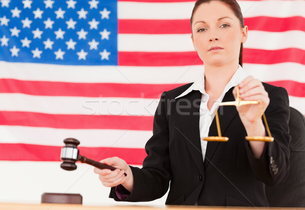 Close up of a cute judge knocking a gavel and holding scales of justice with an American flag in the Stock photo © wavebreak_media