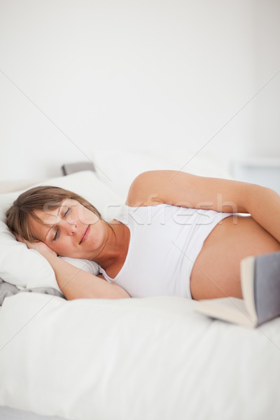Good looking pregnant woman reading a book while lying on her bed in her apartment Stock photo © wavebreak_media