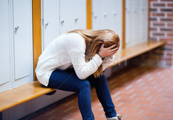 Depressed student sitting on a bench in a corridor Stock photo © wavebreak_media