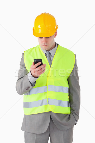 Stock photo: Portrait of a young builder looking at his cellphone against a white background