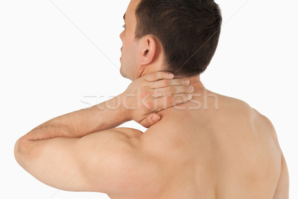 Young man experiencing neck pain against a white background Stock photo © wavebreak_media