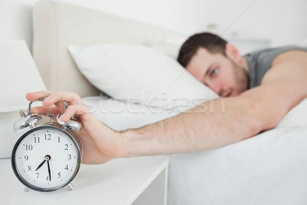 Young man being awakened by an alarm clock in his bedroom Stock photo © wavebreak_media