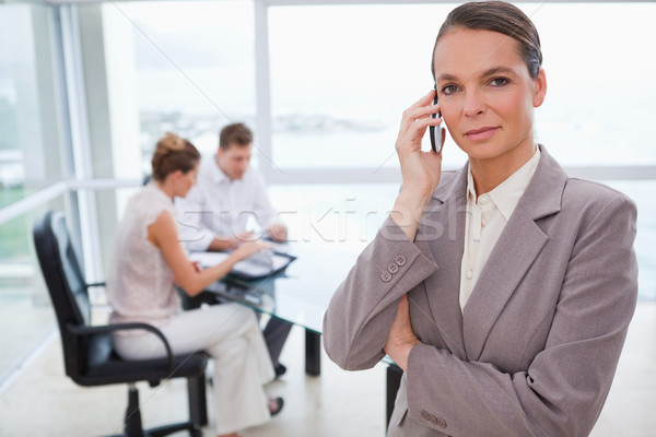 Standing lawyer with cellphone and sitting clients behind her Stock photo © wavebreak_media