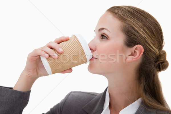 Stock photo: Businesswoman drinking a takeaway coffee against a white background