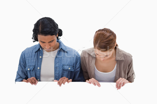 Couple looking down on blank wall against a white background Stock photo © wavebreak_media