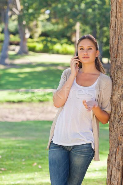 Nő beszél telefon dől fa fiatal nő Stock fotó © wavebreak_media