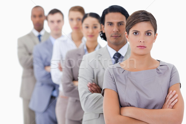 Big close-up of serious workmates in single a line crossing their arms with focus on the first woman Stock photo © wavebreak_media