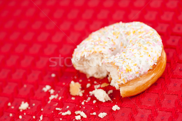 Half eaten doughnut with whipped cream on a red tablecloth Stock photo © wavebreak_media