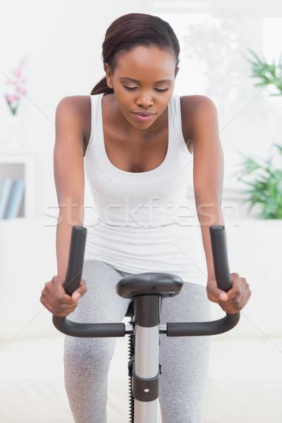 Woman doing exercise bike in a living room Stock photo © wavebreak_media