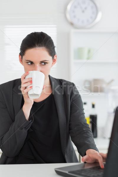 женщину используя ноутбук питьевой кухне компьютер ноутбук Сток-фото © wavebreak_media