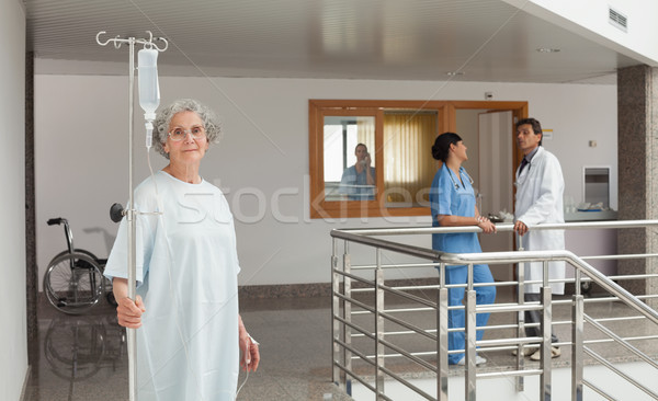 Old woman standing in the hallway in a hospital holding a drip Stock photo © wavebreak_media