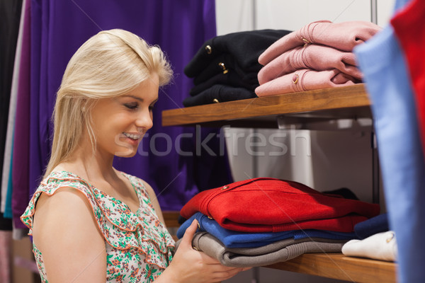 Woman holding clothes at a shelf smiling  Stock photo © wavebreak_media