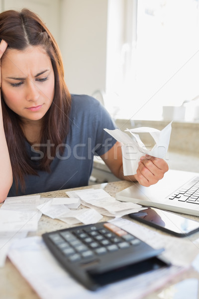 Brunette looking worried and holding bills in kitchen Stock photo © wavebreak_media