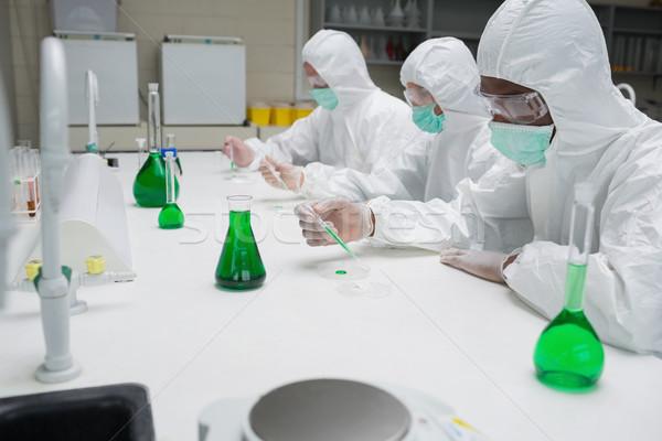 Chemists testing green liquid in petri dishes in the lab Stock photo © wavebreak_media