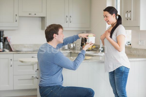 Mujer presente marido uno rodilla cocina Foto stock © wavebreak_media