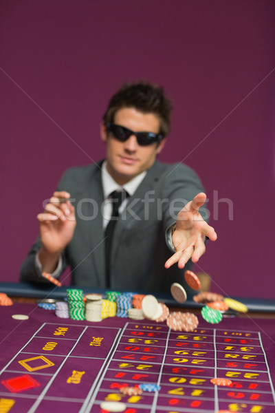 MMan throwing chips on roulette table in casino Stock photo © wavebreak_media