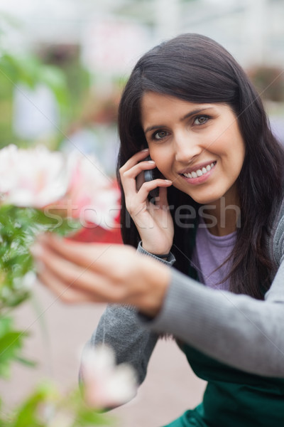 Smiling florist while touching a flower and making a call in the garden centre Stock photo © wavebreak_media