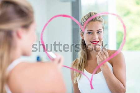 Smiling woman holding a stethoscope while wearing pink uniform Stock photo © wavebreak_media