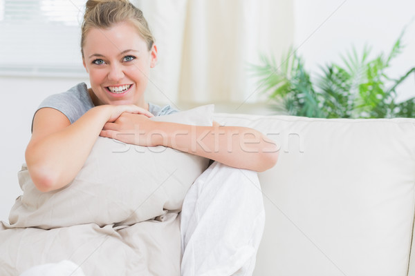 Cheerful woman holding a pillow in living room Stock photo © wavebreak_media