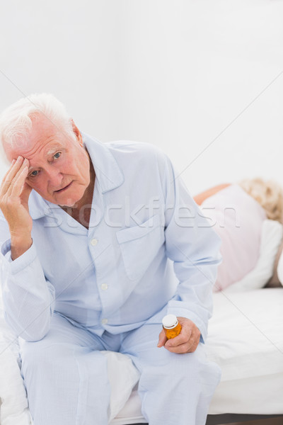 Elderly man suffering while woman sleeping on the bed Stock photo © wavebreak_media