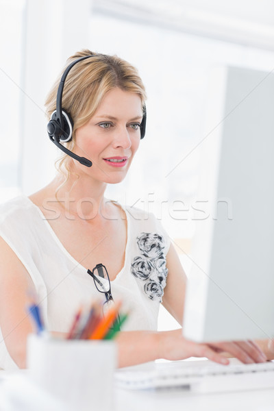 Casual young woman with headset using computer Stock photo © wavebreak_media