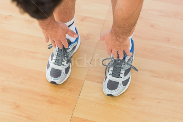 sporty man stretching hands to legs in fitness studio Stock photo © wavebreak_media