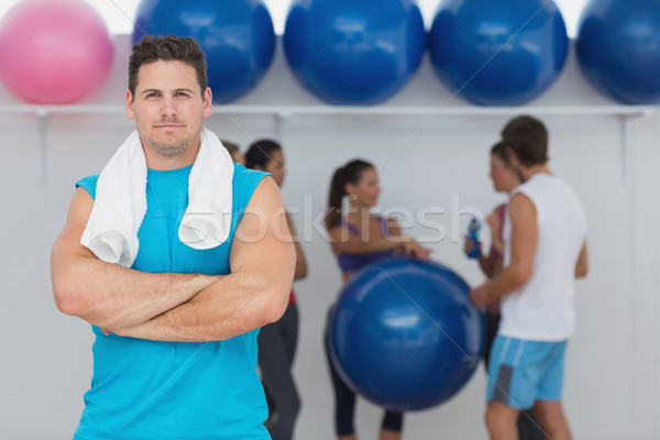 Fit man with friends in background at fitness studio Stock photo © wavebreak_media