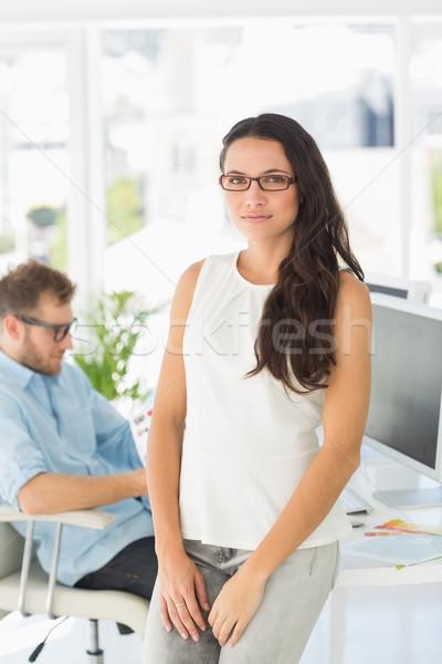Gyönyörű designer mosolyog kamera dől asztal Stock fotó © wavebreak_media
