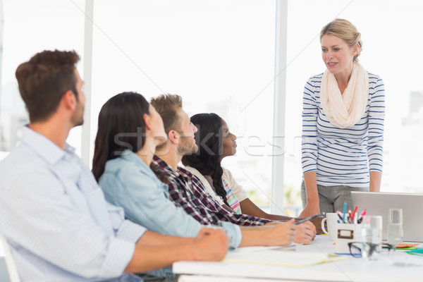 Happy team of young designers listening to boss at meeting Stock photo © wavebreak_media