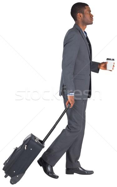 Young businessman pulling his suitcase Stock photo © wavebreak_media