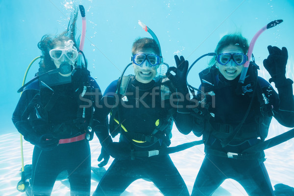 Friends on scuba training submerged in swimming pool making ok s Stock photo © wavebreak_media