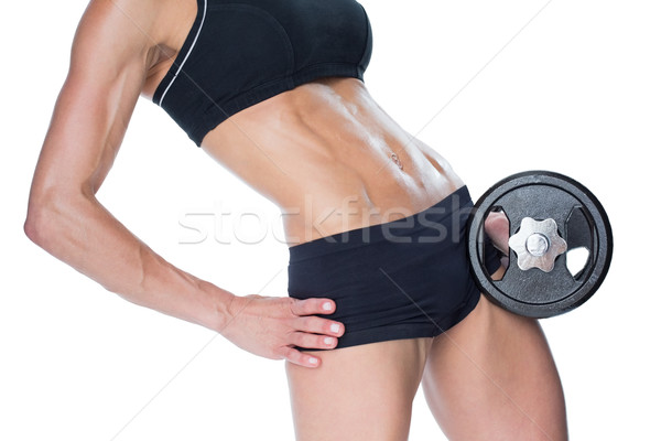 Female bodybuilder holding large black dumbbell mid section Stock photo © wavebreak_media