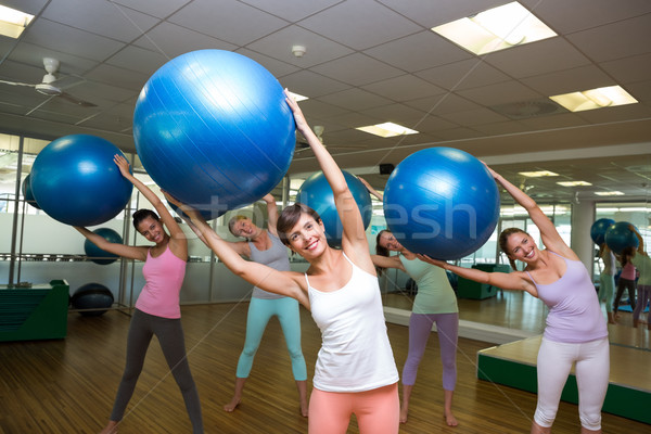 Fitness class holding up exercise balls in studio Stock photo © wavebreak_media