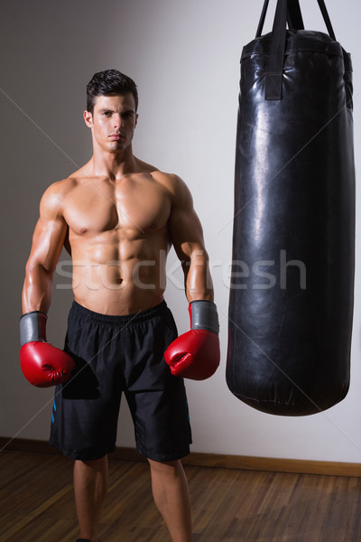 Muscular boxer with punching bag in gym Stock photo © wavebreak_media