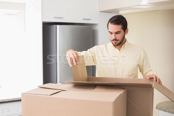 Young man unpacking boxes in kitchen Stock photo © wavebreak_media