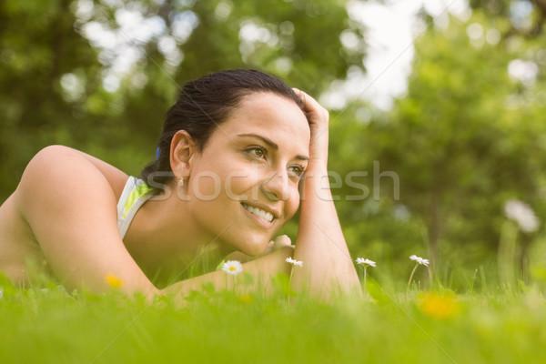 Relaxed fit brunette lying on grass Stock photo © wavebreak_media