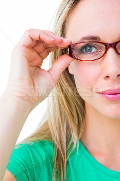 Pretty blonde holding her red reading glasses Stock photo © wavebreak_media