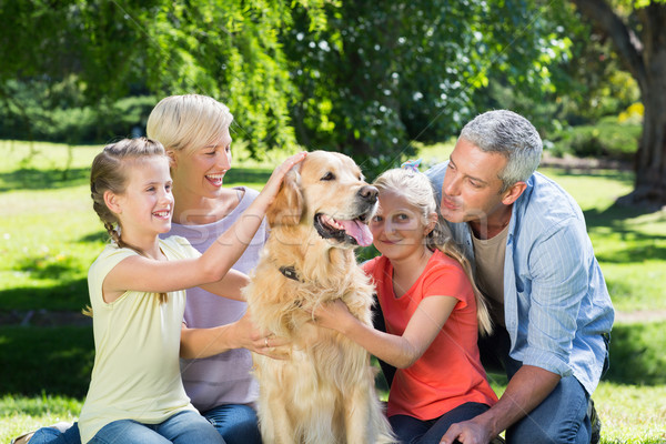 Happy family petting their dog in the park  Stock photo © wavebreak_media