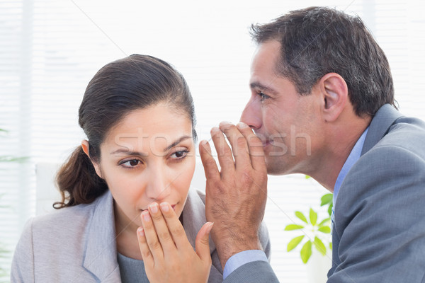 Businessman whispering something to his colleague Stock photo © wavebreak_media