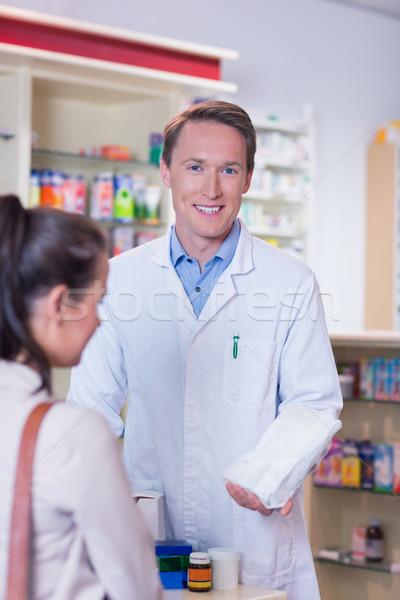 Mosolyog gyógyszerész tart papírzacskó néz kamera Stock fotó © wavebreak_media