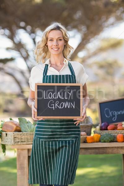 Souriant agriculteur femme augmenté signe Photo stock © wavebreak_media