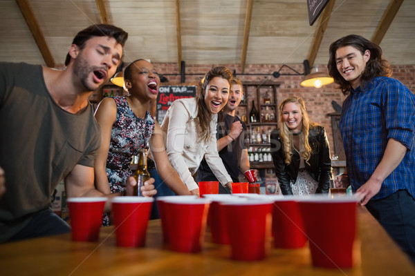 Young friends playing beer pong game in bar Stock photo © wavebreak_media