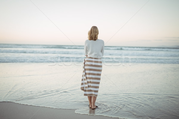 Rear view of woman standing at beach during dusk Stock photo © wavebreak_media