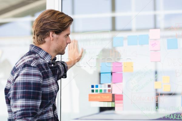 Businessman looking at plan on wall Stock photo © wavebreak_media