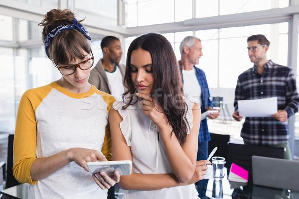 Female colleagues using digital together Stock photo © wavebreak_media