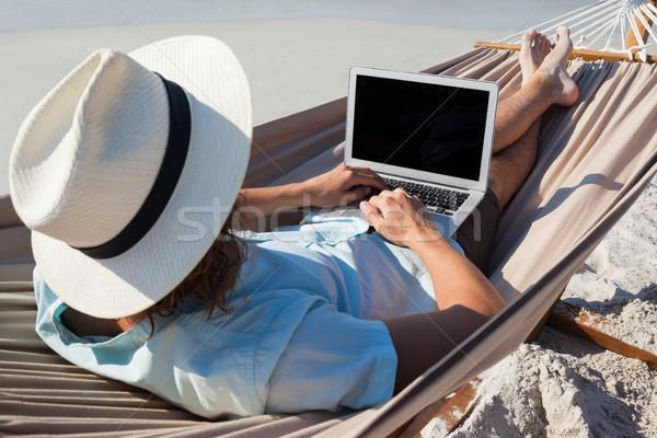 Mann mit Laptop entspannenden Hängematte Rückansicht Strand Stock foto © wavebreak_media