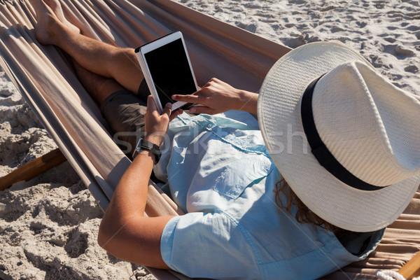 Man ontspannen hangmat digitale tablet strand Stockfoto © wavebreak_media