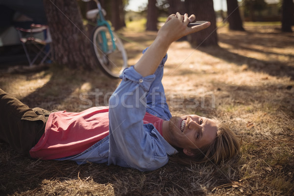 Portrait of man using smart phone while lying on field Stock photo © wavebreak_media