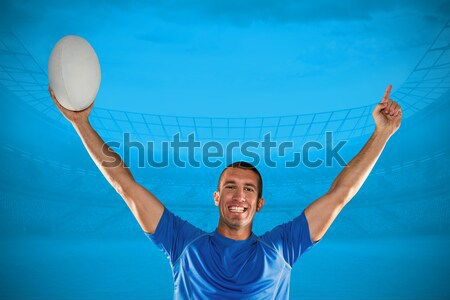 Happy rugby player holding ball with arms raised against blue sky Stock photo © wavebreak_media