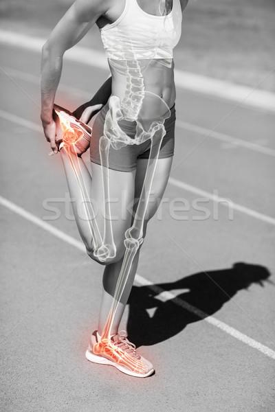 Low section of sportswoman stretching leg on sports track Stock photo © wavebreak_media
